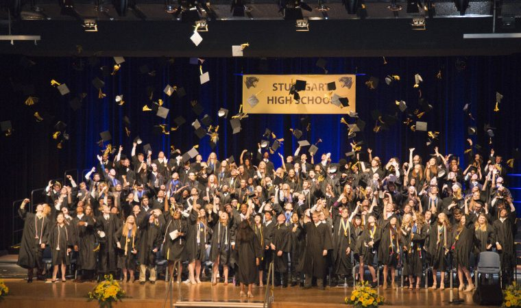 Students perform one last task of  firsts by tossing their mortar boards in the air after moving the tassel from right to left, indicating their status as the  first graduates from the new Stuttgart High School.
