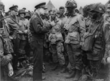 """Eisenhower gives the order of the day to paratroopers in England. """"Full victory -- nothing else"""" was the command just before they boarded their planes to participate in the first wave. The invasion -- code-named Operation Overlord -- had been brewing for more than two years. (Photo Credit: File Photo)"""