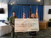 Col. Glenn K. Dickenson, commander, USAG Stuttgart, and Tawania Kovacs, director, ACS, hold a  big check illustrating the savings to the garrison in 2016 thanks to community volunteers. Photo by 1st Lt. Megan Black, 554th Military Police Company, 18th MP Brigade