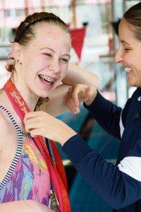 Jane Overslaugh RathbunKim Vandenburg, Olympic medalist, lets Stuttgart Piranhas swim team member Sarah Hutchinson try on a few of her medals.
