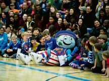 Globie, the official Harlem Globetrotters mascot, takes a break with spectators.
