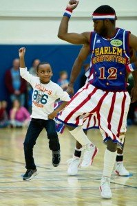 """Tyler Jackson, 7, dances with """"Ant"""" Atkinson after helping the Globetrotter with a trick shot."""