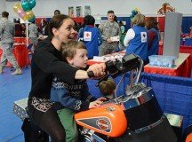 Dina Miller, with her 5-year-old son Kai Miller, enjoy some wild riding during a motorcycle video game that was one of many interactive games at the USAG Stuttgart Resiliency Carnival at Patch Fitness Center Feb. 5.