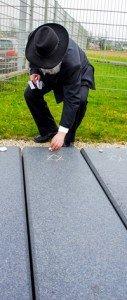 Rabbi Netanel Wurmser, State Rabbi of the Israelite Religious Community Württemberg, places white stones on gravestones during a memorial ceremony at the Jewish gravesite on Stuttgart Army Airfield April 16.