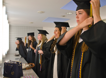 Seniors Madeleine Jones (from left), Gabriella Gante,  Rachel Imlay, Bianca MacMullen and Kyle Hosler take care of last minute touch ups before the commencement exercise starts. Photo by S.J. Grady.