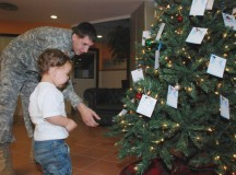 Photo Credit: Laura Kreider A member of the Vicenza Military Community assists a youth in picking an angel off a tree in previous years.