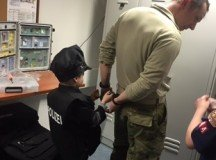 Staff Sgt. Eric Winski gets handcuffed by Cub Scout Pack 44 during their visit to shadow Military Police Officers on Patch Barracks, Feb. 17, 2016.