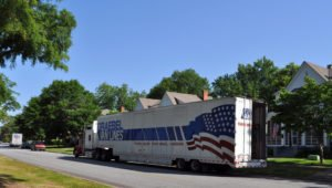 An 18-wheeler unloads household goods; with PCS season upon us, many more trucks will soon be delivering hundreds of tons of personal belongings.