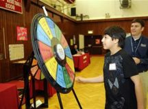 A Kaiserslautern Middle School seventh grade student spins the wheel to find out if he will lose money due to a car accident or win an inheritance during the CU 4 Reality Fair held in the school's gymnasium, Vogelweh Military Complex, Germany, April 30, 2009. Activities like this one taught students how to manage their money responsibly and save up for future incidents that could occur. (U.S. Air Force photo by Senior Airman Amanda Dick)(Released)