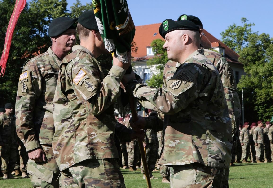 Incoming Commander, Lt. Col. Andrew R. Ries, 1st Battalion, 10th Special Forces Group (Airborne), receives the unit colors from Col. Isaac J. Peltier, commander 10th SFG(A) during the unit's change of command ceremony held on Panzer Kaserne, July 7, 2016. 1st Bn. 10th SFG(A) is one of two forward stationed battalions within Special Forces tracing its history to 10th SFG(A) establishment in Bad Tolz, Germany in 1953. 1st Bn. 10th SFG (A) moved Panzer Kaserne on Aug 1991 where it is still based today. U.S. Army photo by Staff Sgt. Larraine Whetstone
