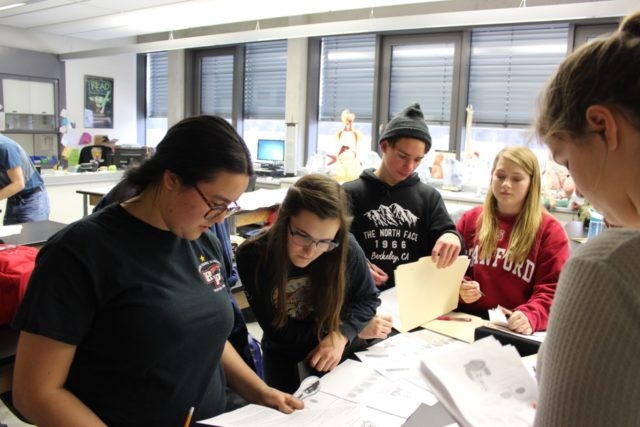 Students sift through evidence to solve a simulated crime.
