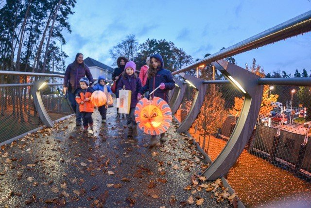 Families walk with lanterns across the pedestrian bridge on Panzer Kaserne to celebrate the German holiday, St. Martin's Day, Nov. 10, 2016. (Photo by Kevin S. Abel, USAG Stuttgart Public Affairs)