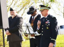 From right, Col. Glenn Dickenson, commander,  U.S. Army Garrison Stuttgart addresses the audience during the Battle of Buchhof ceremony as Larry Nichols and Willie Summers, International Veterans Association Neckarsulm, look on.