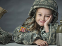 Lily, daughter Army Sgt. James Newby, grins as she poses for portraits with her father's uniform items, March 18, 2015 on Fort Meade, Maryland. (U.S. Air Force photo by Staff Sgt. Vernon Young Jr.)