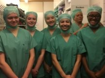 """Rachael Dickensen (SHS'18), Hannah Goldberg (SHS'18), Hannah Cahill (SHS'18), Eve Glenn (SHS'18), and Valen Antoine (SHS'18) ( Left to Right) are aided by Dr. Kessler's assistant to """"scrub in"""" and attend a knee replacement surgery."""