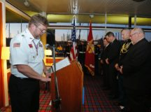 "Joe Holder, chaplain, VFW Post 10810, speaks during the ceremony at the Royal Nautical Club, Barcelona, Jan. 17, 2017. At right, Kerry Dauphinee, who was on the ""Mike"" boat just before the accident, bows his head in remembrance. Photo by the Navy League, Barcelona."