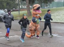 The snow begins to fall as a runner wearing a T-Rex costume, with an ugly sweater, keeps up a steady pace. photos by Larry Reilly, USAG Stuttgart Public Affairs