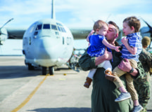 A U.S. Marines with Marine Aerial Refueler Transport Squadron (VMGR) 252 holds his children after returning home from a deployment on Marine Corps Air Station Cherry Point, N.C., March 5, 2018. VMGR-252 returned home from an eight month deployment to Moron Air Base, Spain in support of the Special Purpose Marine Air Ground Task Force. Photo by Marine Corps Cpl. Koby I. Saunders