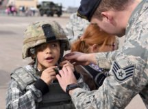 Julia Velez dons a helmet with assistance from Staff Sgt. Zachary Moody, 49th Security Forces Squadron police services, during Operation Kids Investigating Deployment at Holloman Air Force Base, N.M., Feb. 2, 2018. Operation K.I.D. is an annual event that teaches military youth the processes of deployment. (U.S. Air Force photo by Staff Sgt. Timothy Young)