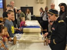 Ch. (Capt.) Karyn Berger (right) uses her yad, or Torah pointer, to highlight a specific passage on the scroll during the Simchat Torah celebration and ark unveiling on October 1. Photo by Bardia Khajenoori, USAG Stuttgart Public Affairs.