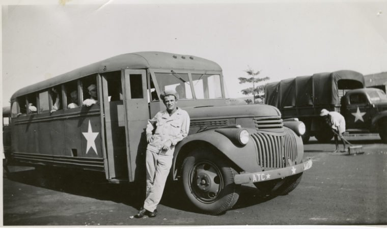 Soldier posing in front of a U.S. Army bus loaded with soldiers possibly near Accra, Ghana in the 1940s. A U.S. Army 2 1/2 ton truck is shown in the background. Possibly members of the Air Transport Corps. Photo from U.S. WW2 Museum
