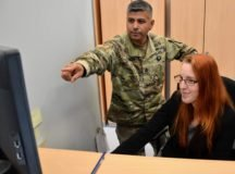 Army Sgt. 1st Class Pablo Escebedo discusses a customer's registration  with Darlene Shattuck, a civilian em- ployee at the USAG Stuttgart vehicle  registration office. Wait times now for customers are minimal, staff said.
