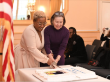 """Journi, at left, member of the local musical group """"PB&J,"""" joins garrison deputy to the commander Kathryn E. McNeely to cut the cake in observance of Dr. Martin Luther King Jr., Jan. 23. Photo by AFN Stuttgart"""