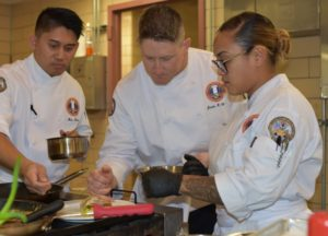 Group of chefs hover over sauce pans