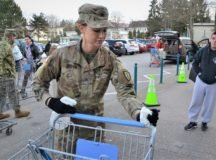 Service members like U.S. Army Sgt. Trista Urban support garrison efforts to combat COVID-19, by limiting the number of shoppers at the Patch Barracks' commissary, reminding people about handwashing and wiping down carts. Photo by Rick Scavetta, USAG Stuttgart.