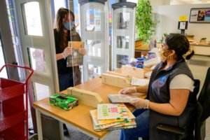 Librarian with face mask helps customer