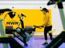 A Stuttgart fitness center employee on Panzer Kaserne, Stuttgart, Germany, maneuvers a spin bike to set up future socially distanced spin classes. FMWR gyms are expected to reopen shortly in Stuttgart after being closed for several weeks during the COVID-19 pandemic. (photo by Paul Hughes, USAG Stuttgart)