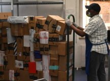 A postal worker at the Patch Community Mail Room moves packages for sorting.