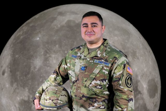 An officer stands in front of an image of the moon
