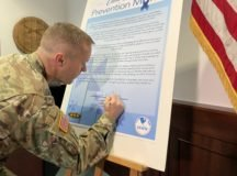 U.S. Army Garrison Stuttgart Commander, Col. Jason Condrey, signs a proclamation to recognize April as Child Abuse Awareness and Prevention Month. Photo by Paul hughes