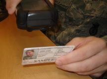 A soldier uses a scanner to scan an ID.