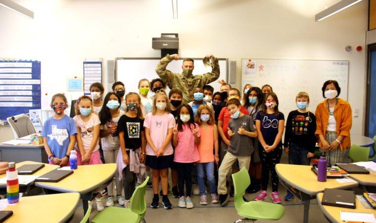 Col. Matt Ziglar, USAG Stuttgart garrison commander poses with students after a visit to Stuttgart Elementary School.